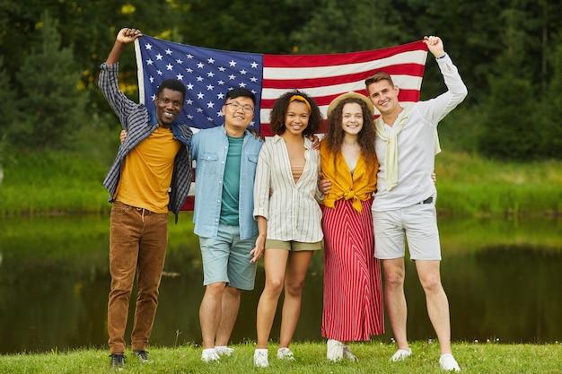 Porträt in voller länge der multiethnischen gruppe von freunden, die amerikanische flagge halten, während party im sommer genießen
