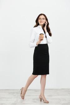 Porträt in voller länge der schönen jungen geschäftsfrau in der formellen abnutzung, die für handy mit kaffee zum mitnehmen in der hand geht und spricht