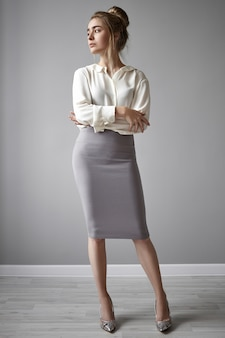 Porträt in voller länge der schönen selbstbewussten erfolgreichen jungen chefin, die stilvolle schuhe mit hohen absätzen, midirock und weißes formelles hemd trägt, wegschaut und arme auf ihrer brust verschränkt hält