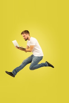 Porträt in voller länge des glücklichen springenden mannes lokalisiert auf gelbem hintergrund. kaukasisches männliches modell in freizeitkleidung
