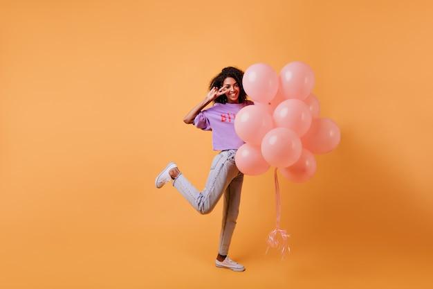Porträt in voller länge des inspirierten afrikanischen mädchens, das auf einem bein mit luftballons steht. gut gelaunte hübsche dame, die geburtstag feiert.
