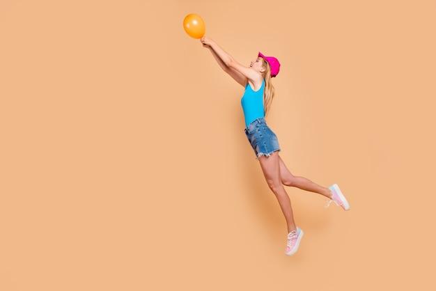 Porträt in voller länge des jungen aufgeregten mädchens, das mit gelbem luftballon auf beige fliegt