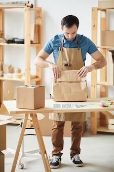 Porträt in voller länge des reifen mannes, der schürzenverpackungsaufträge trägt, während er durch holztisch, lebensmittel-lieferservice-arbeiter steht