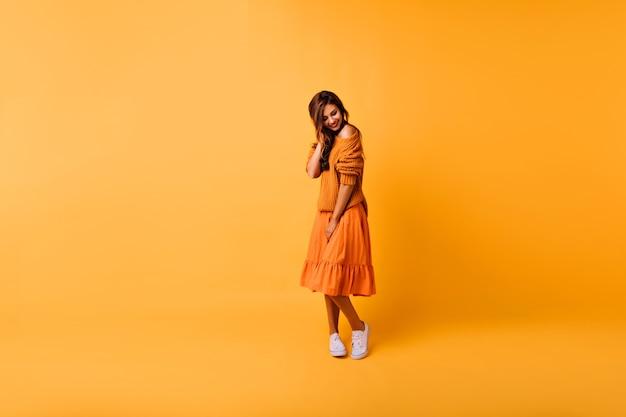 Porträt in voller länge des schüchternen kaukasischen mädchens, das auf gelb steht. innenaufnahme des siegreichen mädchens im orange gestrickten pullover und im rock.
