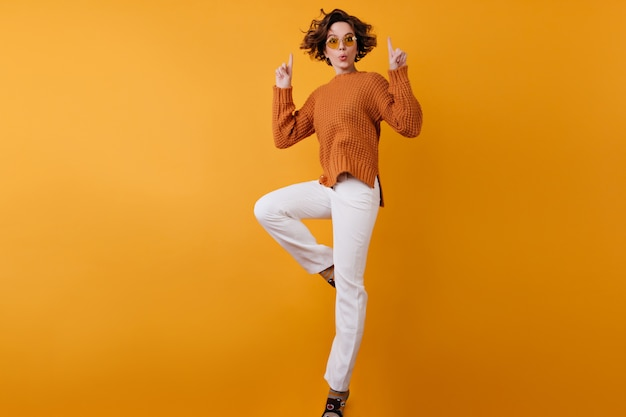 Porträt in voller länge des sorglosen mädchens in der weißen hose, die auf orange raum springt