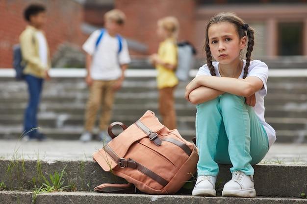 Porträt in voller länge des traurigen schulmädchens, das kamera betrachtet, während auf treppen draußen mit gruppe von kindern im hintergrund, kopienraum sitzt