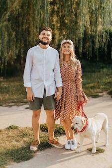 Porträt in voller länge des verheirateten paares, das mit ihrem weißen labrador im park vor dem hintergrund der weide aufwirft.