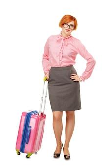 Porträt in voller länge einer geschäftsfrau in gläsern in geschäftsreise, die mit einem rosa reisekoffer steht