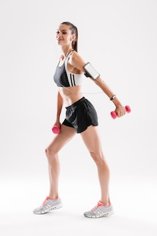 Porträt in voller länge einer glücklich lächelnden fitnessfrau