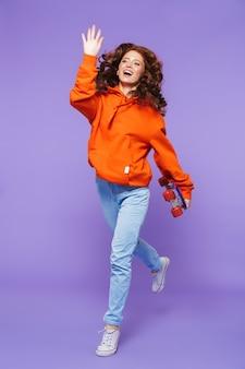 Porträt in voller länge einer hübschen jungen rothaarigen frau, die über veilchen springt und skateboard hält
