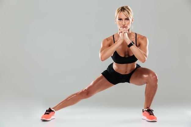 Porträt in voller länge einer jungen selbstbewussten fitnessfrau