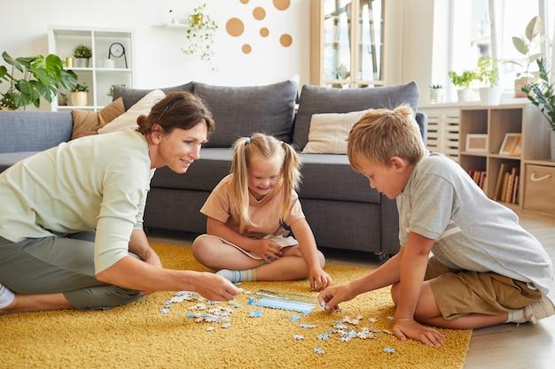 Porträt in voller länge einer liebevollen familie mit einem kind mit besonderen bedürfnissen, das brettspiele und rätsel spielt, während es zu hause auf dem boden sitzt und platz kopiert