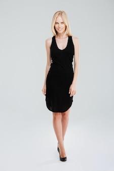 Porträt in voller länge einer modeglücklichen frau, die im schwarzen kleid lokalisiert auf einem weißen hintergrund aufwirft