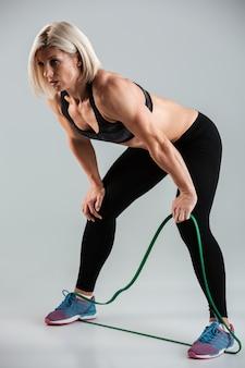 Porträt in voller länge einer müden muskulösen erwachsenen sportlerin, die sich ausruht