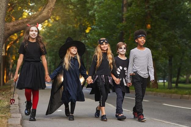 Porträt in voller länge einer multiethnischen gruppe von kindern, die auf der straße gehen, während süßes oder saures an halloween