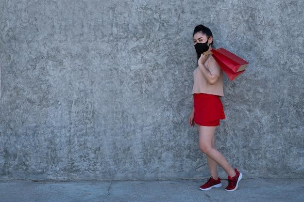 Porträt in voller länge einer schönen jungen asiatischen frau, die eine gesichtsmaske mit einkaufstüten an der betonwandwand trägt, tragen frauen rosa kleidung und roten rock, der die kamera betrachtet
