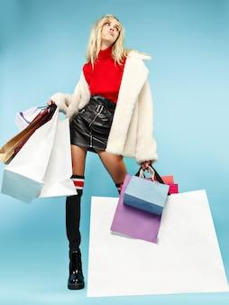 Porträt in voller länge einer schönen lächelnden lustigen blonden frau, die mit bunten einkaufstaschen über blauem studiohintergrund lokalisiert geht.