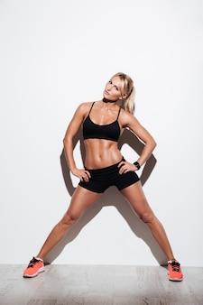 Porträt in voller länge einer selbstbewussten muskulösen sportlerin, die aufwirft