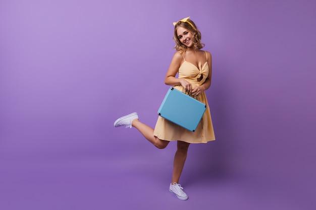 Porträt in voller länge eines erfreuten gebräunten mädchens mit blauem koffer. ansprechende dame im gelben kleid, das auf einem bein steht.