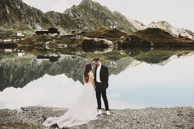 Porträt in voller länge eines erstaunlichen paares in ihrem hochzeitstag nahe einem see in den bergen, die einander lächelnd schauen.