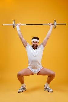Porträt in voller länge eines fitnessmannes, der mit langhantel hockt