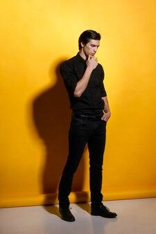 Porträt in voller länge eines gutaussehenden starken jungen mannes des athleten in der schwarzen kleidung auf gelbem hintergrund. vertikale ansicht.