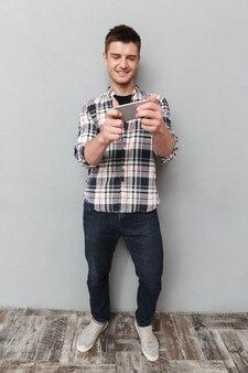 Porträt in voller länge eines lächelnden jungen mannes, der spiele spielt