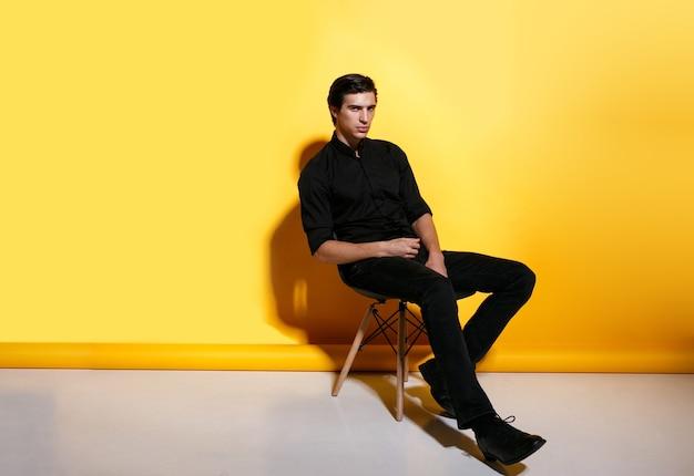 Porträt in voller länge eines mode-mannes, der auf stuhl sitzt und kamera betrachtet, im studio auf gelbem hintergrund posierend. horizontale ansicht.