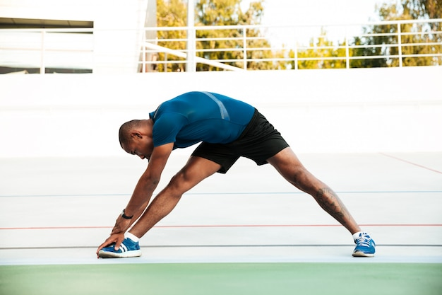 Porträt in voller länge eines motivierten sportlers, der sich streckt