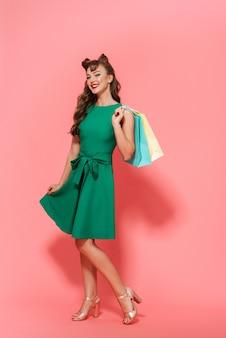 Porträt in voller länge eines schönen jungen pin-up-mädchens, das ein kleid trägt, das isoliert steht und einkaufstaschen trägt