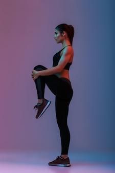 Porträt in voller länge im profil der kaukasischen frau mit dem schlanken starken körper, der training tut und ihre beine streckt, lokalisiert über bunte wand