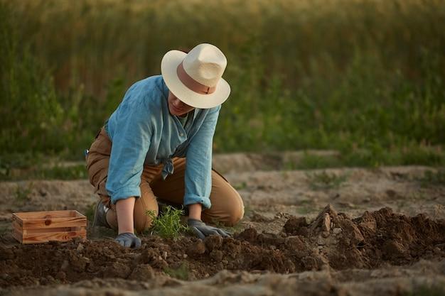 Porträt in voller länge von bäuerin, die gemüse auf dem feld oder auf der plantage pflanzt, kopierraum