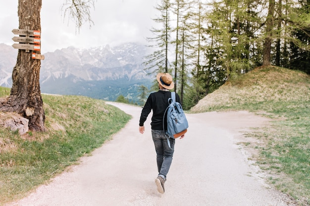 Porträt in voller länge von der rückseite des gehenden männlichen reisenden, der die italienische natur während des urlaubs genießt