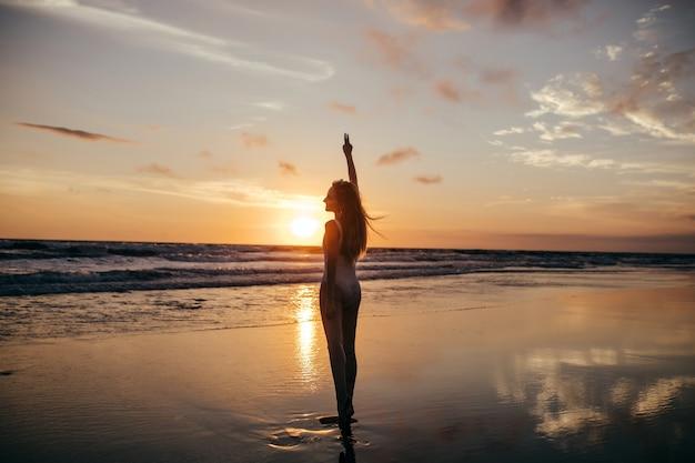 Porträt in voller länge von der rückseite des mädchens, das den sonnenuntergang im meer betrachtet. außenaufnahme des erfreuten weiblichen modells, das am abend an der ozeanküste kühlt.