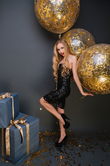 Porträt in voller länge von entzückendem geburtstagskind mit goldenen luftballons, die etwas feiern. innenfoto der erfreuten blonden dame, die nahe geschenkboxen aufwirft.