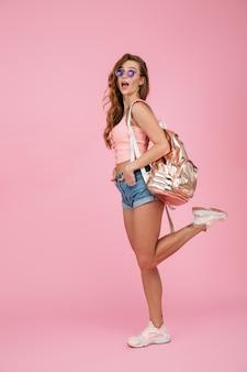 Porträt in voller länge von erstaunter lesekopffrau in der sommerkleidung mit rucksack, stehend auf einem bein mit händen in ihrer tasche
