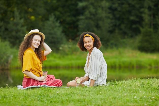 Porträt in voller länge von zwei jungen frauen, die auf grünem gras durch wasser sitzen, während sie urlaub im sommer genießen
