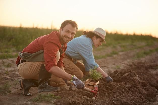 Porträt in voller länge von zwei personen, die im feld an der gemüseplantage arbeiten, fokus auf jungen mann, der setzlinge im vordergrund pflanzt und in die kamera lächelt, raum kopieren