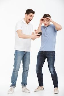 Porträt in voller länge von zwei überraschten jungen männern