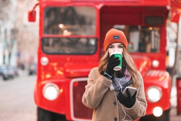 Porträt in warmer winterkleidung steht mit einer tasse kaffee und einem smartphone in den händen vor dem hintergrund der stadtlandschaft