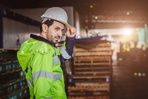 Porträt intelligenter lateinischer arbeiter im logistiklager des frachthafens, der mit sicherheitsanzug selbstbewusst steht.
