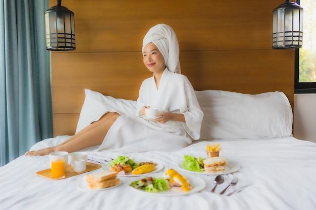Porträt junge asiatische frau auf bett mit frühstück im schlafzimmer