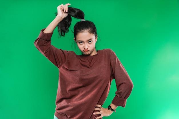 Porträt junge asiatische frau, die stirnrunzelndes gesicht ausdrückt, während sie ihr langes schwarzes haar hochhält und zur kamera auf grüner wand schaut
