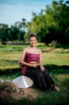 Porträt junge asiatische frau in schöner thailändischer traditioneller kleidung am reisfeld