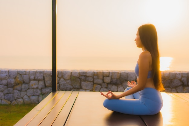 Porträt junge asiatische frau machen meditation um meer strand ozean bei sonnenaufgang