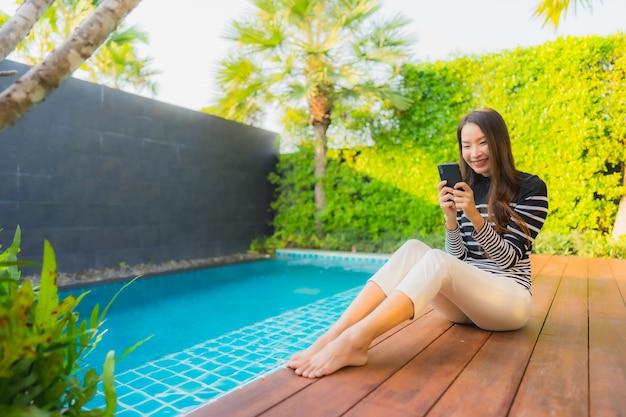 Porträt junge asiatische frau unter verwendung des intelligenten mobiltelefons um außenschwimmbad