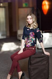 Porträt junge attraktive frau, die auf koffern im terminal oder am bahnhof sitzt. das mädchen traf sich auf einer reise.