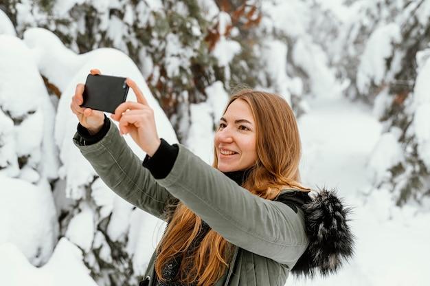 Porträt junge frau am wintertag, der foto macht