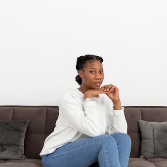 Porträt junge frau, die auf couch sitzt