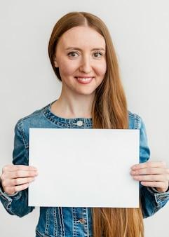 Porträt junge frau, die papierblatt hält Kostenlose Fotos